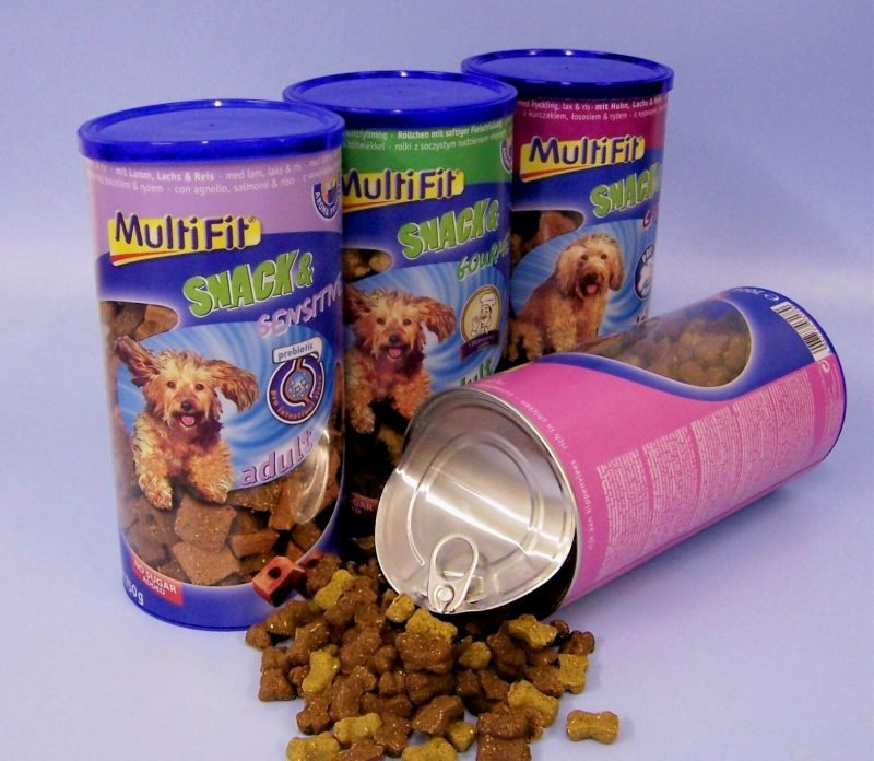 4 large coloured packaging tins of dry dog food,. One tin spilled out.